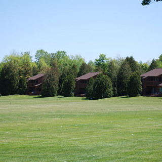 Townhouses among trees in front of a grass field
